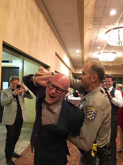 "Attorney Darren Kavinoky gets ""arrested"" all in good fun at the annual CHP Christmas Party, December 2015."