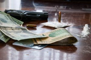 table with drugs, money, and a pistol on top