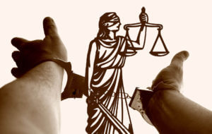 handcuffs against the scales of justice